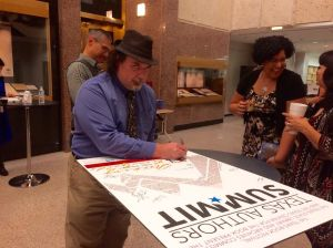Jon Black signs the authors' poster at the 2016 Texas Authors' Summit.